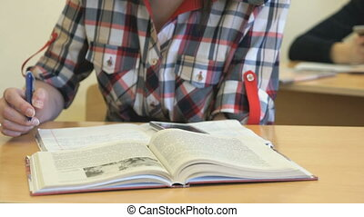 Student sitting at desk writes text in copybook