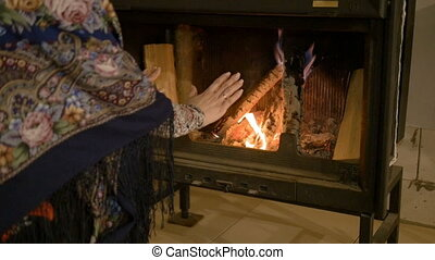 Home comfort. Woman warming his hands by the fire. Warm in winter.