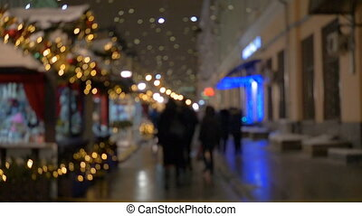 People walking on the street in the evening, a festive illumination, out of focus