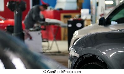 Mechanic in car service fixing and repairing detail of automobile, defocused background