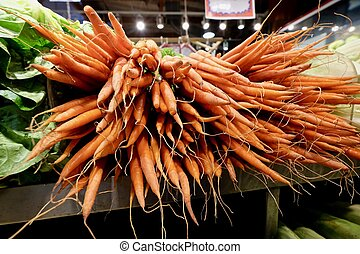 Organic carrots on market shelves. - Granville Island...