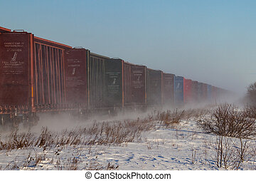Line of Empty Railcars Whipping up Snow - A line of empty...