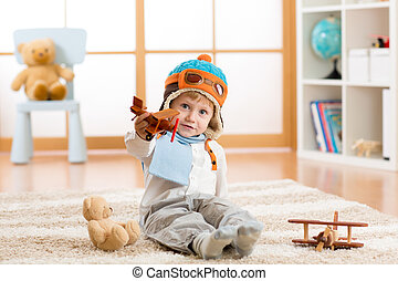 Happy child boy playing with wooden toy airplane and teddy bear on floor in nursery room