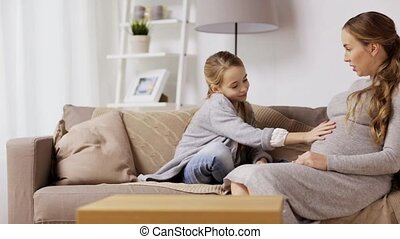 pregnant woman and girl listening to baby at home -...