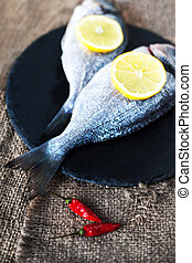 Fresh raw Dorado sea fish on wooden table with lemon and red...