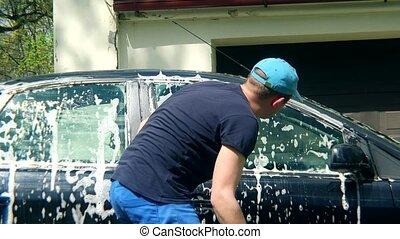 Man worker washing car with sponge on a car wash near...