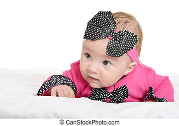 Adorable baby girl on blanket in cute pink clothes on a...