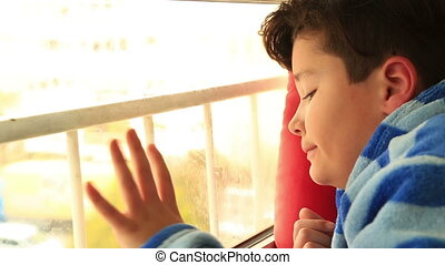 A young boy sits looking out the window - Sad child sitting...