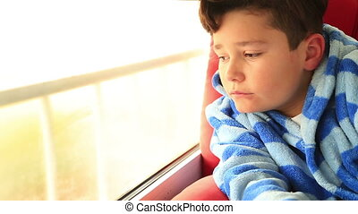 A young boy sits looking out the window - The sad boy the...