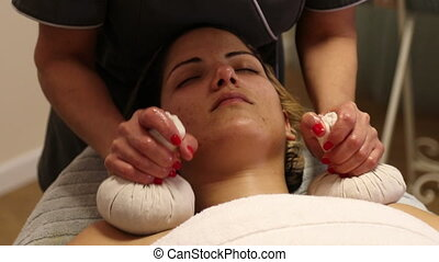 Masseuse uses herbal compressing balls - Herbal compressing...