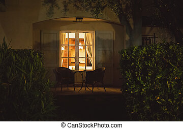 House door at night. Table and two chairs outdoor. Be home...