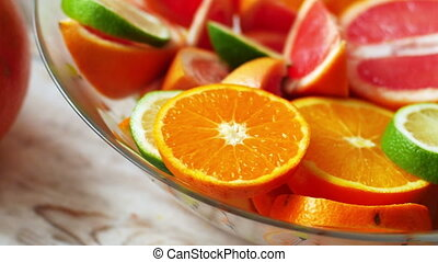 Oranges, limes, tangerines and grapefruit in bowl on wooden...