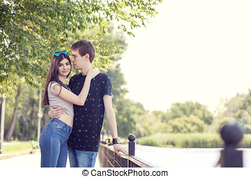 Happy young inlove couple talking a walk in the park near a...