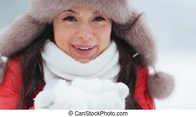 happy woman playing with snow outdoors in winter