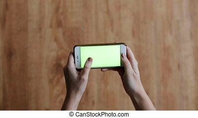 hands with chroma key green screen on smartphone - people...