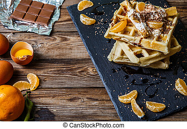 Wooden table with Belgian waffles, tangerines, chocolate