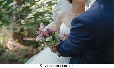 Bride and groom pose in the wood. Closeup view of wedding...