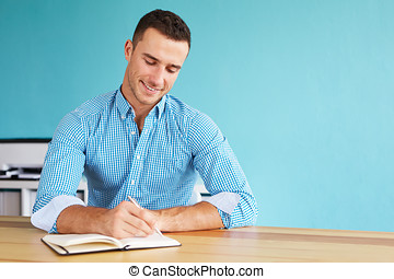 Young happy man sitting in his office and writing plan in...