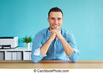 Portrait of a young man in the office, leaning on hands