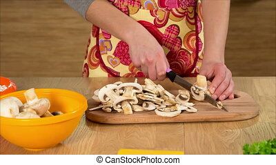 Closeup of girl hands cutting the moshrooms in kitchen -...