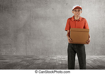 Cheerful asian courier standing with parcel