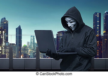 Hooded hacker with vendetta mask stealing information with...