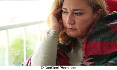 Sad young woman looking through window - Unhappy middle aged...