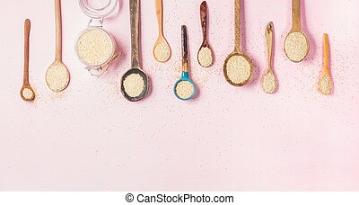 Quinoa seeds in different spoons and glass jar, copy space -...