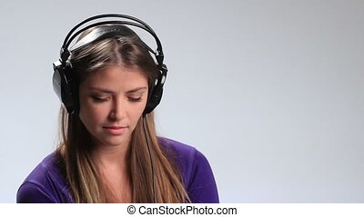 Enjoying her favorite music in earphones - Beautiful young...