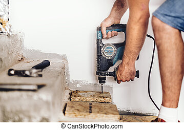 industrial construction worker drilling holes in wooden board and concrete using professional machinery