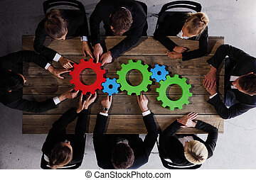 Business people gathering cogs - Group of business people...