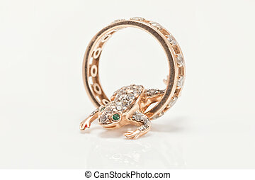 Golden pendant in the shape of a frog crawls in a gold ring...
