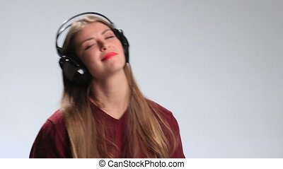 Happy cheerful girl enjoying music in headphones - Beautiful...