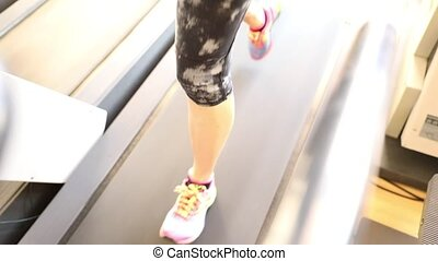 The treadmill run - Slow motion of woman legs in colorful...