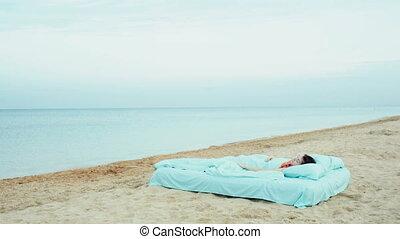 Girl wakes up on the beach