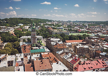 Blue cloudy sky and town. Trees and buildings. Townscape at...