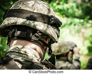 US Army Soldiers on mission in the woodland. Old color film...