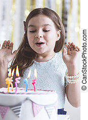 Girl blowing out birthday candles - Happy small girl blowing...