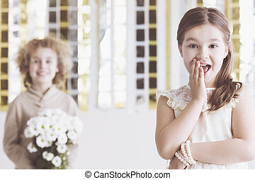 Little flirty girl and small wooer with flowers