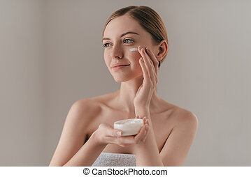 Taking good care of her skin. Gorgeous young woman looking away and smiling while standing against background