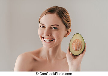Perfect for her skin. Beautiful young woman with freckles on face holding avocado and looking at camera while standing against grey background