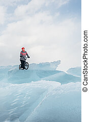 Girl on a bmx on ice. - Girl standing on a bmx on the...