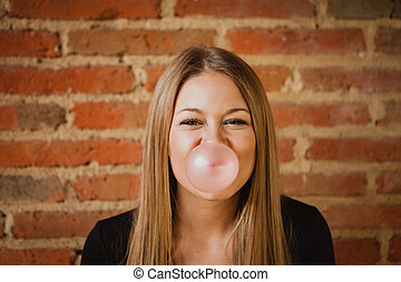 Funny girl making a pomp with a bubble gum and a brick wall...