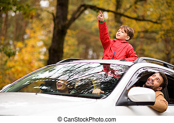 Adorable boy standing in car sunroof - Adorable smiling boy...