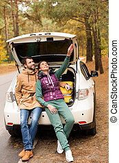 Smiling couple sitting in car trunk - Smiling young couple...
