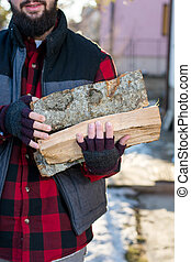 Man carrying firewood in the yard - Man carrying firewood in...