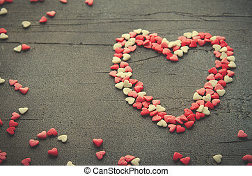 Heart made with small candy hearts, pink, red, whie colors,...