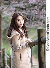 beautiful asian young woman in blooming cherry blossoms sakura