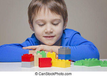 Little kid boy playing with colourful plastic construction...