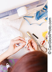 Girl with cloth in hand in studio with sewing machine